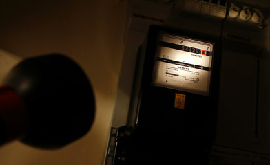 A man points a flashlight towards the electricity meter of his household for this illustration picture in Hanau, 35km south of Frankfurt