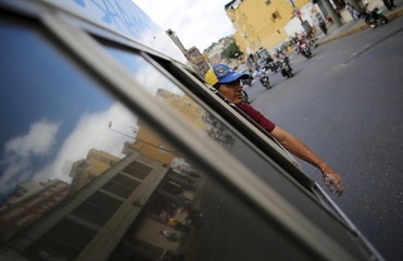 An opposition supporter travels by van after gluing posters of candidates from the Venezuelan coalition of opposition parties in Caracas