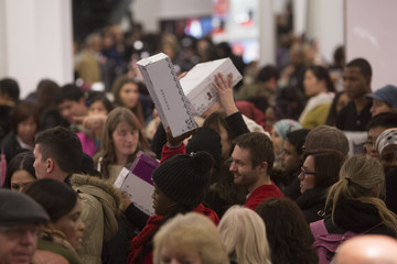 People carry shoes in Macy's during Black Friday sales in New York