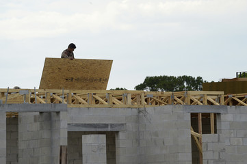 Workers construct a new home in the Balmoral neighborhood being developed by Irishman Garrett Kenny