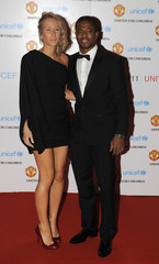 Manchester United's Evra and wife Sandra arrive for the UNICEF Gala Dinner at Old Trafford Stadium in Manchester