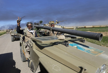 Shi'ite fighters ride a vehicle as they take control at the town of Tal Ksaiba, near the town of al-Alam