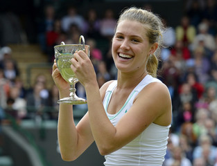 Eugenie Bouchard of Canada holds her trophy after defeating Elina Svitolina of Ukraine in their girls' final tennis match at the Wimbledon tennis championships in London