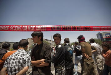 Onlookers stand near the site of a suicide blast in Kabul