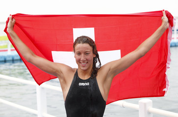 Oberson of Switzerland holds Swiss national flag after winning women's 5km open water race during 14th FINA World Championships in Shanghai