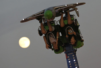 The moon is seen in the background as people ride upside down at the Wisconsin State Fair in West Allis