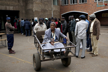 Majika is transported on a push cart after casting her vote in Mbare township
