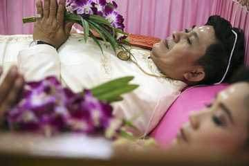 A groom and a bride hold flowers inside a pink coffin during their wedding ceremony at Wat Takien temple in Nonthaburi province