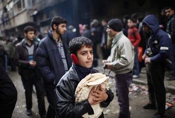 A boy holds pita bread as others stand in line outside a bakery in Aleppo