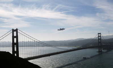 Retired space shuttle Endeavour is carried on the back of a NASA jet as it approaches the Golden Gate Bridge in San Francisco