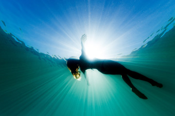 A beautiful woman floats on her back in the ocean as she is surrounded be bright ethereal light and sun rays.