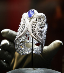 A staff member ajusts a watch with diamonds of the collection Merveilles du Nil on the Cartier booth during the opening day at the Salon International de la Haute Horlogerie in Geneva