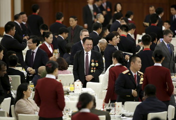 A delegate with medals looks for his seat ahead of a reception marking China's 66th National Day at the Great Hall of the People in Beijing