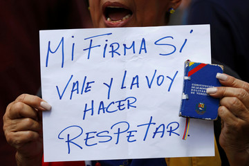 """An opposition supporter holding a copy of the Venezuelan constitution and a sign that reads, """"My signature is valid and it deserves respect"""", shouts slogans during a gathering to demand a referendum to remove President Maduro in Caracas"""