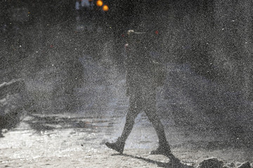 A woman walks through a gust of blowing snow in frigid cold temperatures though downtown Chicago