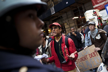 An Occupy Wall Street demonstrator asks police officers why protestors are not allowed to walk down the sidewalk of Broad Street during a protest against the rising national student debt, in New York