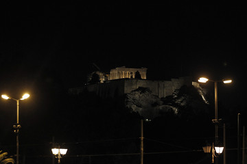 Street lights are seen in front of the illuminated Parthenon temple in Athens