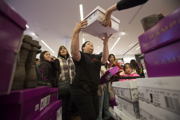 Sales assistant distributes shoes in Macy's during Black Friday sales in New York