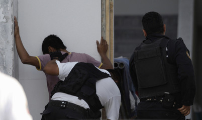 Police detectives search a man for weapons near a branch of local newspaper El Norte in the municipality of San Pedro Garza