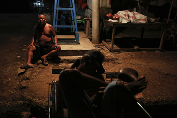 Rickshaw and bus drivers sleep in the open air outside Yangon