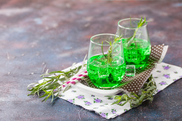 Drink from an estragon with ice in a glass on a table. Selective focus. Copy space