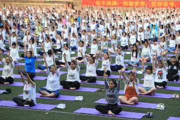 Chinese high school students practice yoga at a schoolyard in Chongqing