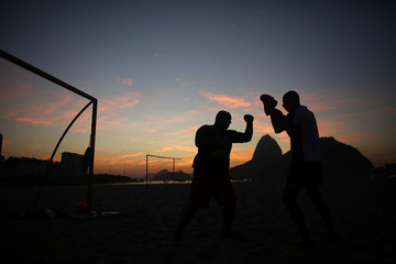 Men practise boxing in the early morning on Botafogo beach, with Sugar Loaf mountain in the background, in Rio de Janeiro