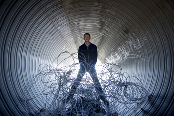 Gay rights activist Slavsky poses for a photograph in a construction pipe at the beach in Sochi
