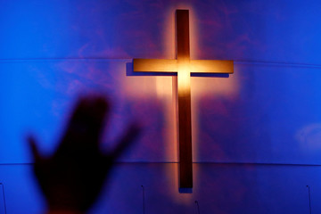 A woman's hand is seen in silhouette during a prayer service at the Concord Baptist Church in Dallas, Texas