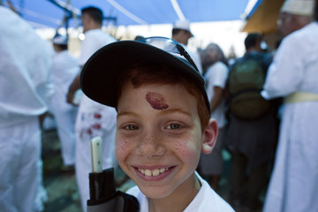 Boy, who is member of Samaritan sect, poses for photo with sheep bloodstain on his forehead during traditional Passover sacrifice ceremony on Mount Gerizim