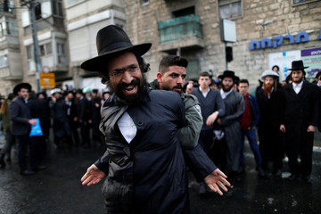 Ultra-Orthodox Jewish protestor is detained by an Israeli border policeman during a demonstration against members of their community serving in the Israeli army, in Jerusalem