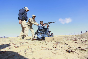 Police officers practise firing their weapons at a shooting range during a refresher training programme in Najaf