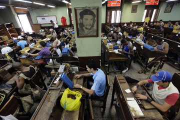 Workers roll cigars at the Partagas factory near a picture of revolutionary leader Che Guevara in Havana