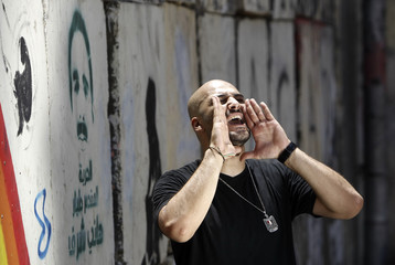 Mohamed El Deeb, a 28-year-old rap and hip hop singer, performs during the making of his music video, in front of a wall with graffiti near Tahrir square in Cairo