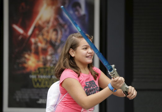 A child plays with a light saber outside the Star Wars Launch Bay grand opening at Disney's Hollywood Studios in Orlando