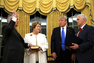 New U.S. Secretary of State Rex Tillerson is sworn in by U.S. Vice President Mike Pence as his wife Renda St. Clair holds a Bible, accompanied by U.S. President Donald Trump during a ceremony at the Oval Office of the White House in Washington, U.S.