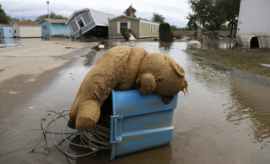 A stuffed teddy bear chair lies slumped over in the flooded Eastwood Village in Evans, Colorado