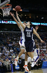 Cougars' Fredette shoots as Gators' Parsons and Yeguete defend in the second half of their NCAA Southeast Regional college basketball game in New Orleans