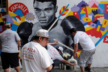 Employees of Joe's Pizza build a makeshift memorial to the late Muhammad Ali near a mural in New York