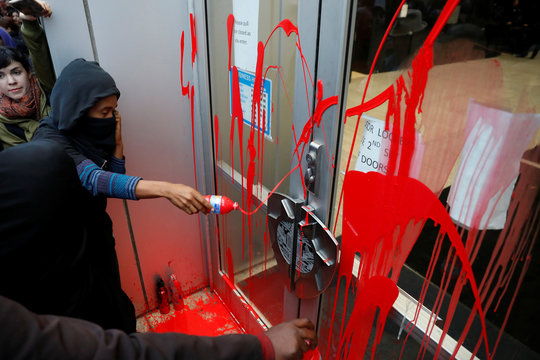 Demonstrators splash red paint on a door outside Oakland Police headquarters during a protest against the police shootings that lead to two deaths in Louisiana and Minnesota, respectively, in Oakland, California