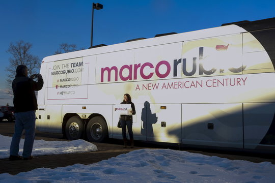 A woman poses for a picture in front of the U.S. Republican presidential candidate Senator Rubio's bus during a visit to a Miami Dolphins versus New England Patriots watch party in Atkinson, New Hampshire