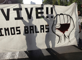 People from civil organizations are silhouetted as they hold a banner during a protest demanding justice for the death of two students in Ayotzinapa, during a march on streets in Mexico City