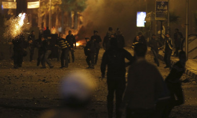 Protesters flee from rubber bullets and teargas fired by riot police in Port Said city