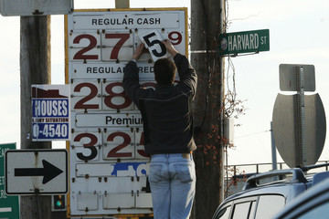 A man changes the price for a gallon of gasoline at a gas station in Medford