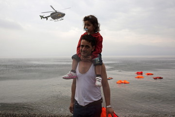 A Syrian refugee carries his daughter as a Frontex helicopter flies over on the Greek island of Lesbos