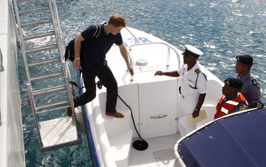 Britain's Prince Harry boards a boat for Harbour Island in Nassau
