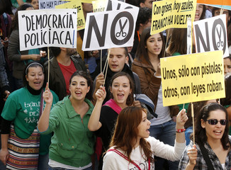 Students hold signs and shout slogans during a student strike to protest against education cuts in Madrid