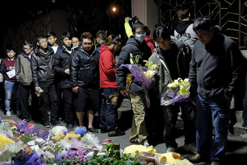 People line up to place bunches of flowers at a makeshift memorial near the site where a girl was found decapitated, outside a metro station, in Taipei, Taiwan