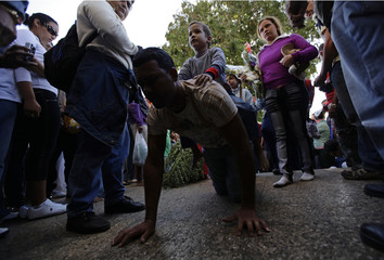 A man crawls with his son on his back in penitence at the entrance of the shrine of Saint Lazarus in the town of Rincon