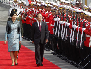 Chinese Premier Wen and Thai PM Yingluck review a guard of honour at the Government House in Bangkok